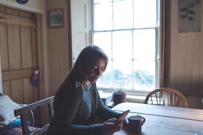 Frau benutzt Handy beim Kaffee zu Hause — Stockfoto