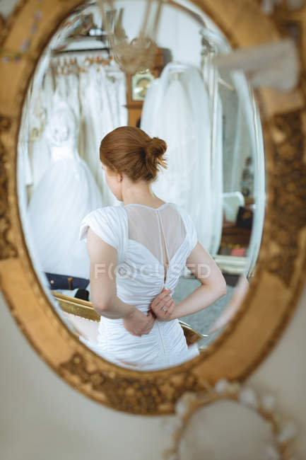 Reflection in mirror of red hair bride adjusting wedding dress zipper on back — Stock Photo