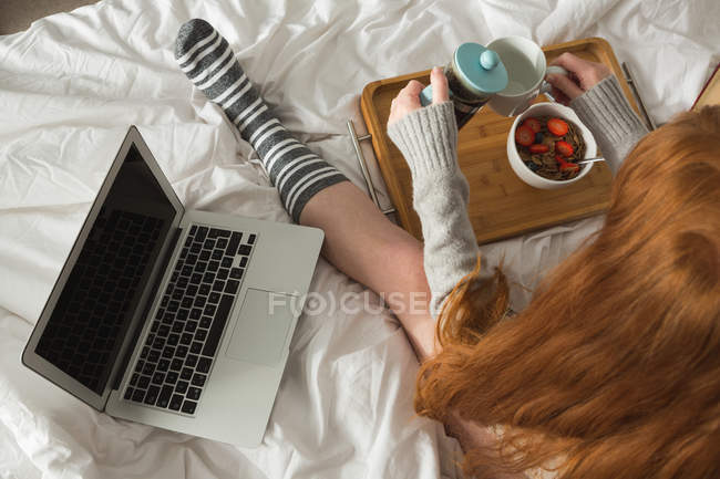 Женщина пьет черный кофе в спальне дома — стоковое фото