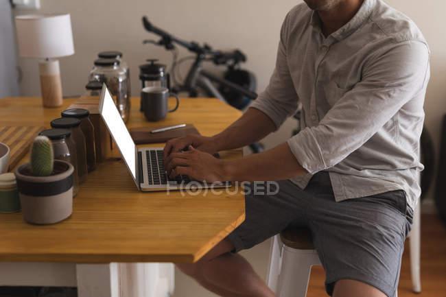 Розділ середині людина, використовуючи ноутбук на дому — стокове фото