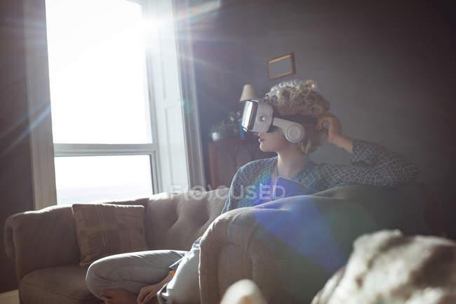 Жінка за допомогою віртуальної реальності гарнітуру у вітальні на дому — стокове фото