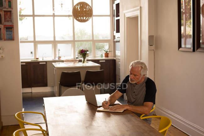 Aktiven senior Mann schreiben auf ein Tagebuch zu Hause — Stockfoto