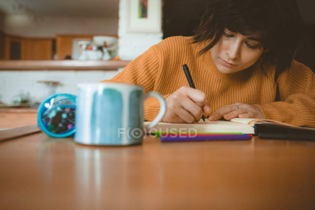 Woman drawing a sketch in a book at home — Stock Photo