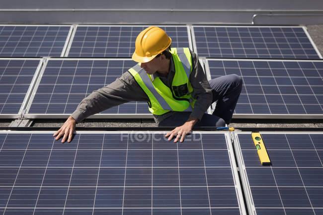 Мужчина работает на солнечных батареях на солнечной станции в солнечный день — стоковое фото