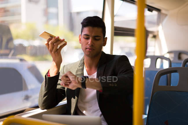 Businessman checking time while talking on mobile phone in bus — Stock Photo