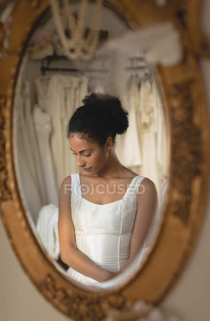 Reflection of young bride in wedding dress in mirror — Stock Photo
