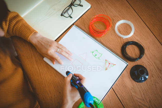 Mid section of woman drawing a sketch in a book at home — Stock Photo