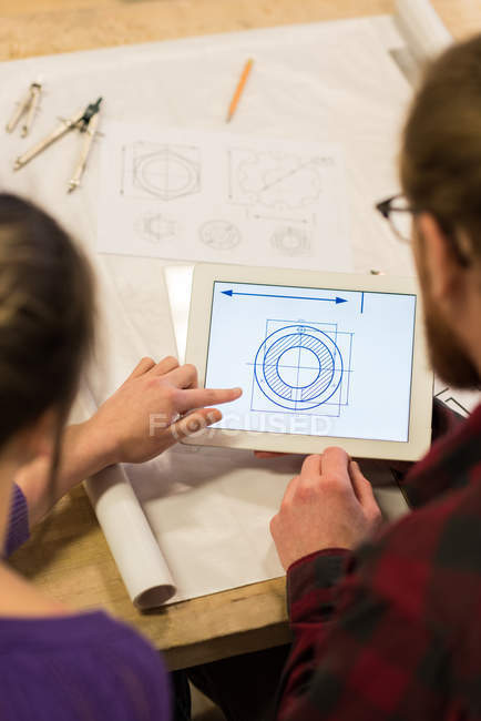 Male and female carpenters looking at plan on digital tablet in workshop — Stock Photo