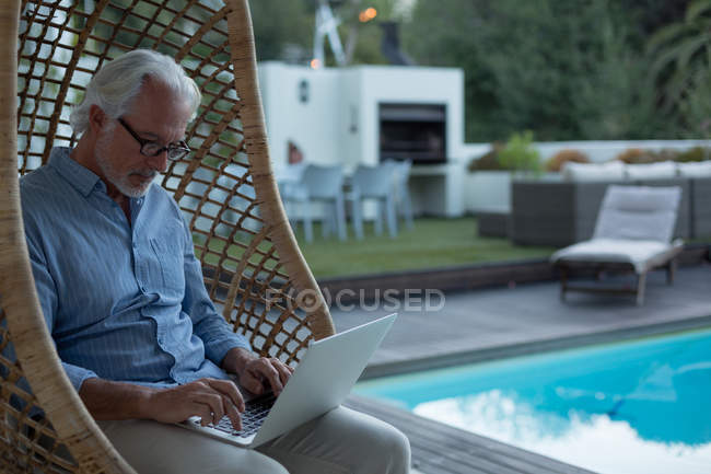 Active senior man using laptop near poolside — Stock Photo