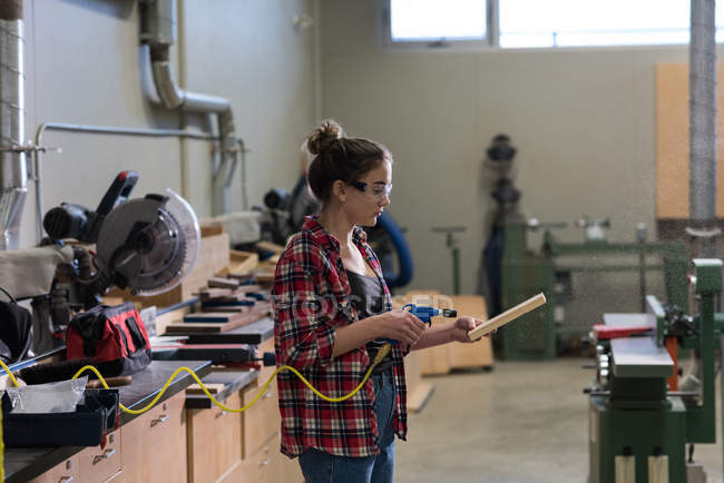Female carpenter using a machine on a piece of wood at workshop — Stock Photo