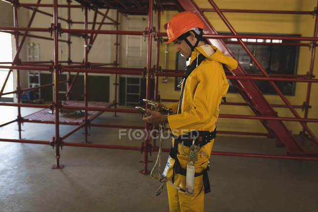 Young male worker holding carabiner at solar station — Stock Photo