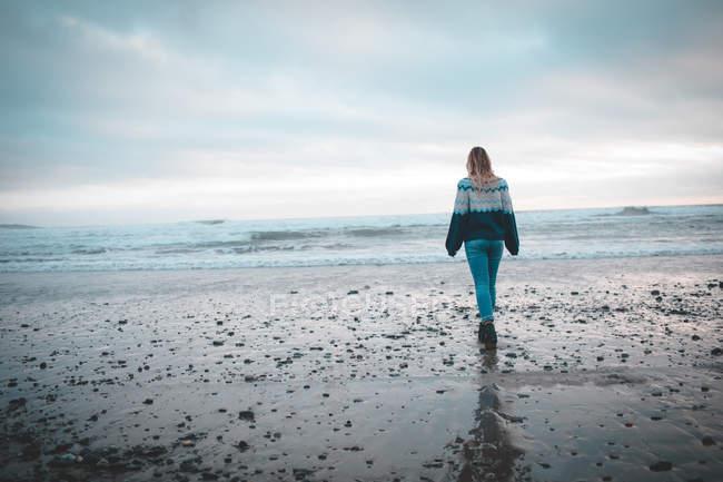 Rückansicht einer Frau, die am Strand spaziert — Stockfoto