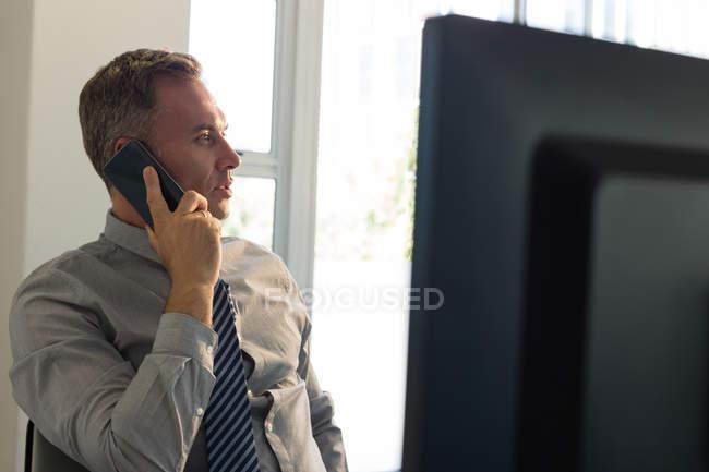 Бизнесмен разговаривает по мобильному телефону за столом в офисе — стоковое фото