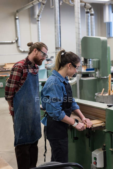 Male and female carpenters working together on vertical cutter machine at workshop — Stock Photo