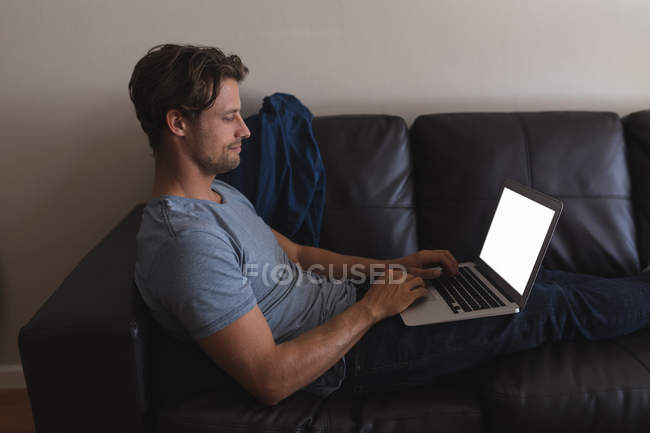 Man using laptop in living room at home — Stock Photo