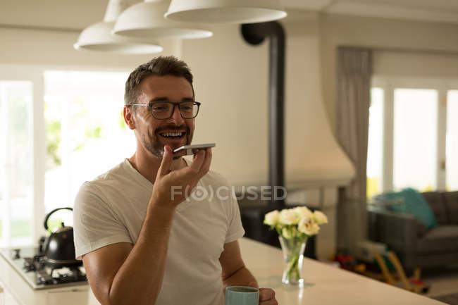 Man talking on mobile phone at home — Stock Photo