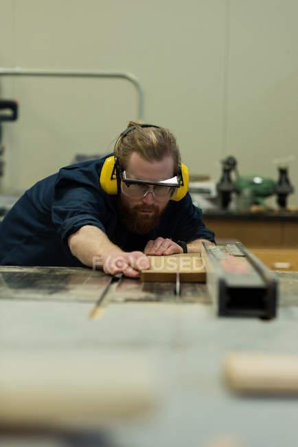 Male carpenter taking measurement of wood at workshop — Stock Photo