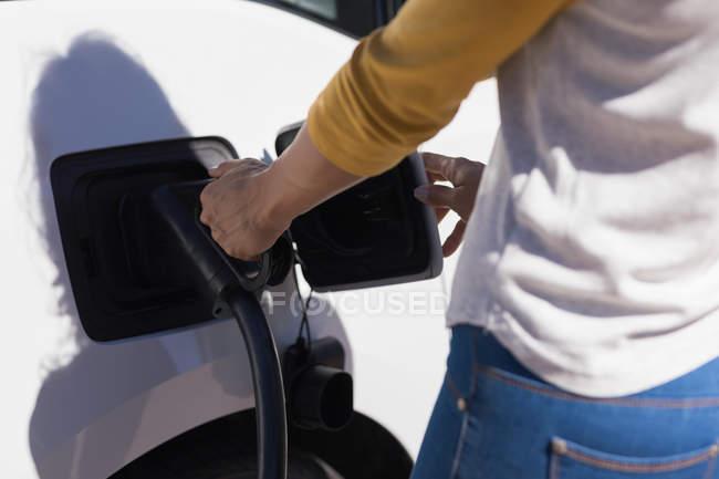Section médiane de femme recharge voiture électrique à la station de recharge — Photo de stock
