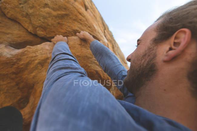 Hombre excursionista escalando montaña rocosa en el campo en un día soleado - foto de stock