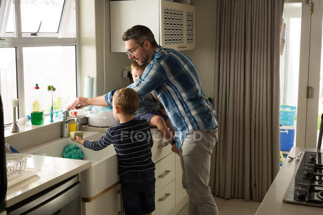 Father and son cleaning sink in kitchen at home — Stock Photo