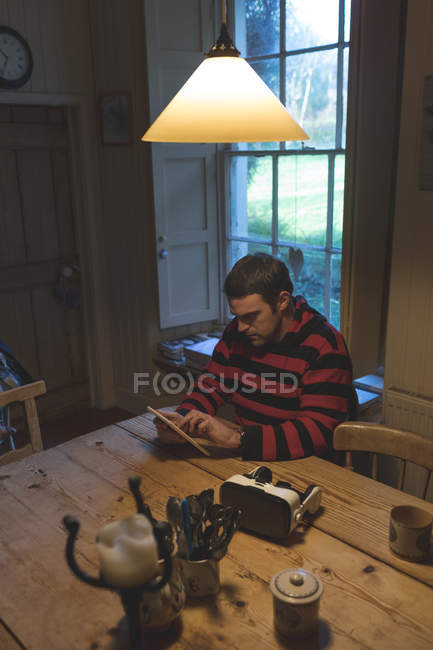 Attentive man using digital tablet at home — Stock Photo