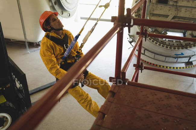 Young male worker climbing scaffolding at solar station — Stock Photo