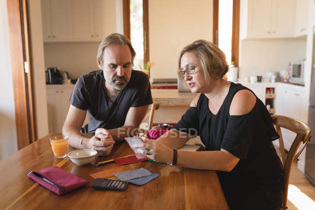 Couple calculating invoice bills in kitchen at home — Stock Photo