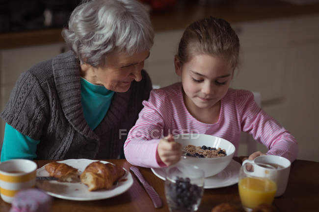 Grandmother and granddaughter having breakfast in kitchen at home — Stock Photo