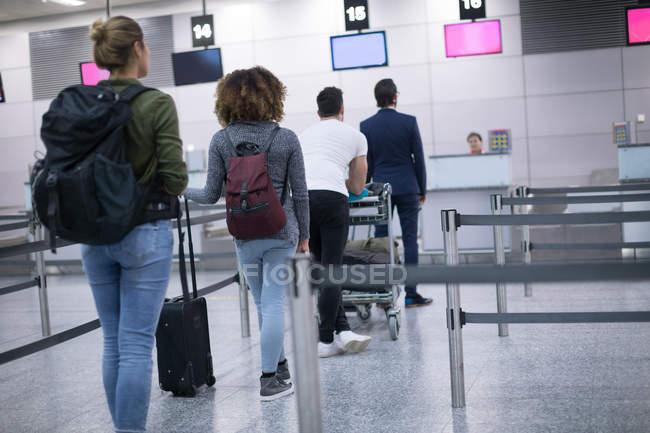 Commuters em fila para check-in no aeroporto — Fotografia de Stock