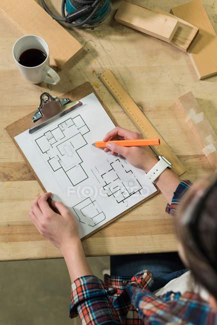 Falegname femminile che disegna un piano sugli appunti in officina — Foto stock