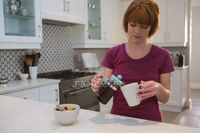 Woman pouring coffee into mug in kitchen at home — Stock Photo