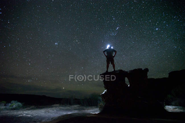 Male hiker standing with hands on hip in countryside at night — Stock Photo