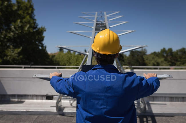 Rear view of male worker using machine at solar station — Stock Photo