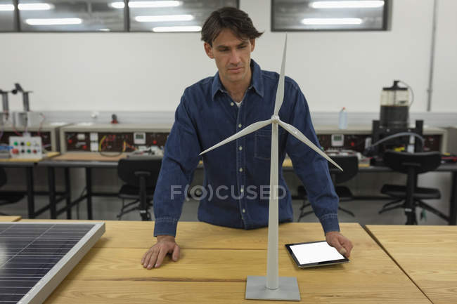 Male worker working on windmill in office — Stock Photo