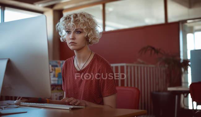 Jeune femme travaillant sur ordinateur à la bibliothèque — Photo de stock