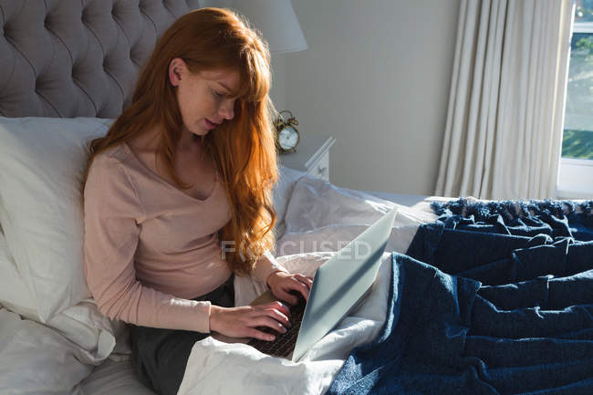 Woman with red hair using laptop in bedroom at home — Stock Photo