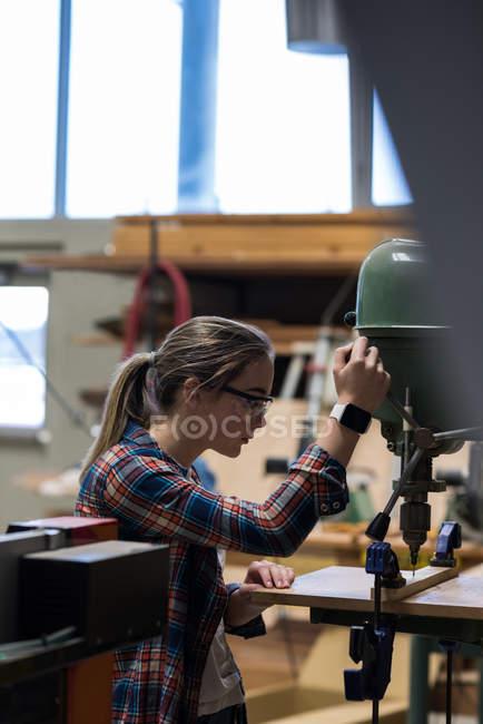 Carpinteiro feminino usando máquina de broca vertical na oficina — Fotografia de Stock