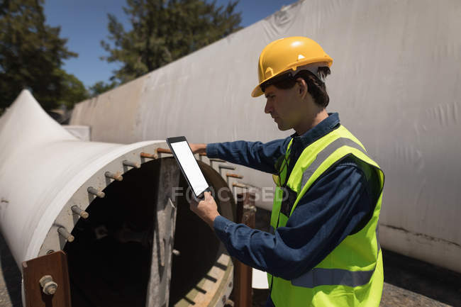 Male worker using digital tablet while examining concrete tunnel at solar station — Stock Photo