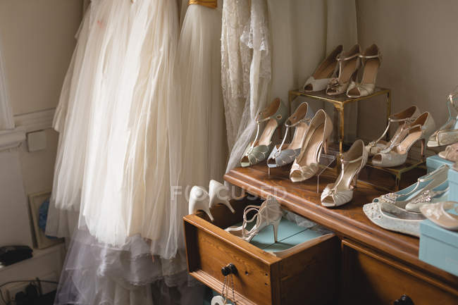 Various wedding dresses and footwear in boutique — Stock Photo