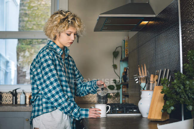 Young woman pouring coffee into mug at home — Stock Photo