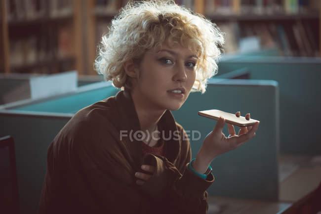 Retrato de mulher falando no celular na biblioteca — Fotografia de Stock