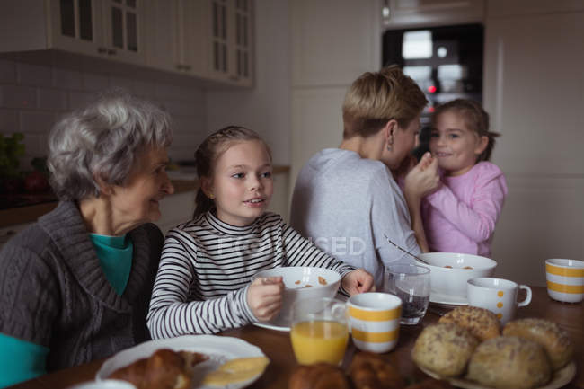 Multi-generation family having breakfast in kitchen at home — Stock Photo