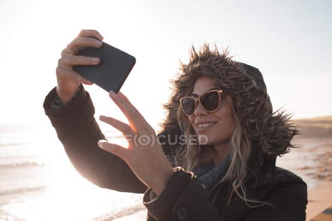 Jeune femme prenant selfie avec téléphone mobile à la plage — Photo de stock