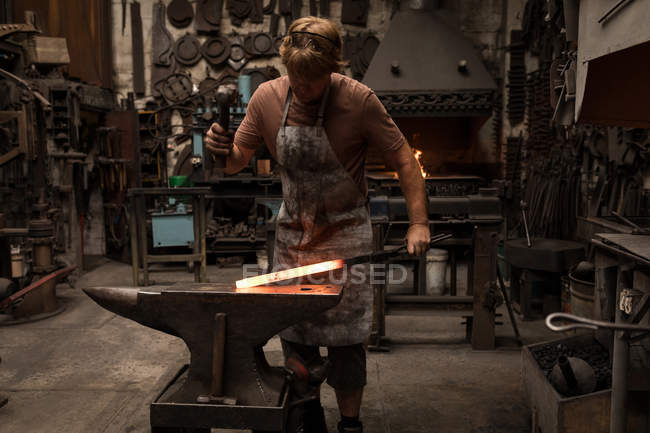 Blacksmith hammering a hot metal rod in workshop — Stock Photo