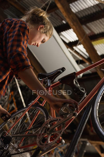 Female mechanic examining a bicycle in workshop — Stock Photo