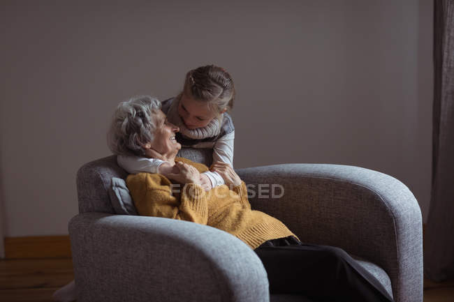Granddaughter embracing her grandmother in living room at home — Stock Photo