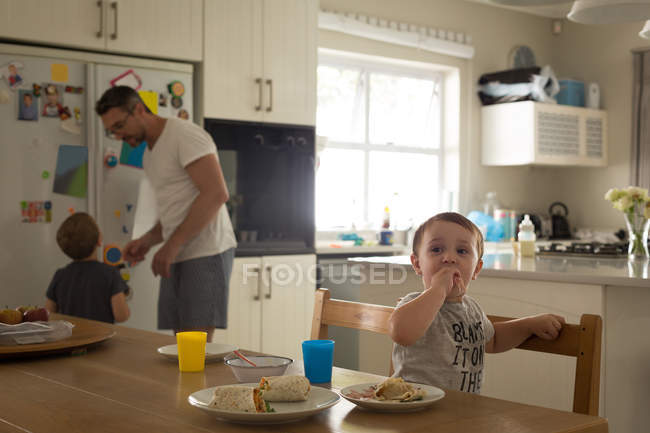Baby boy having breakfast while father and brother interacting with each other at home — Stock Photo