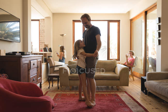 Father daughter dancing together in living room at home — Stock Photo