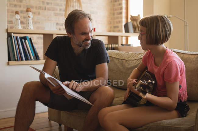 Father helping her daughter to play guitar in living room — Stock Photo