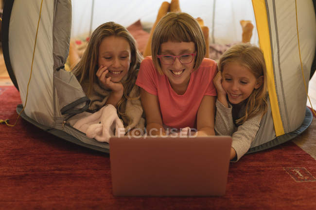 Happy siblings using laptop in a tent at home — Stock Photo